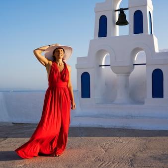 Rot gekleidete frau in oia, santorini, griechenland.