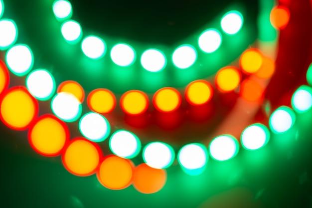 Rot-gelb-grüne neon-bokeh-lichter. festlicher hintergrund von retro-farben.