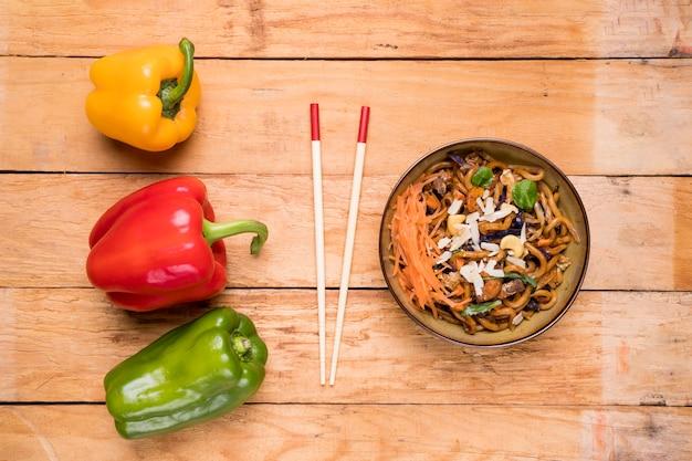 Rot; gelbe und grüne paprikaschoten mit essstäbchen und udon-nudeln auf tisch