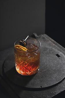 Rot-gelber alkoholischer cocktail mit nüssen, pflaumen und zitrone in einem dunklen retro-interieur