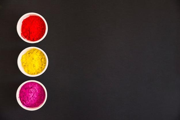 Rot; gelbes und rosafarbenes holi farbpulver in der weißen schüssel auf schwarzem hintergrund