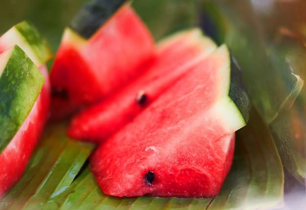 Rot geschnittene wassermelone mit samen im natürlichen bananenblattaufschlag