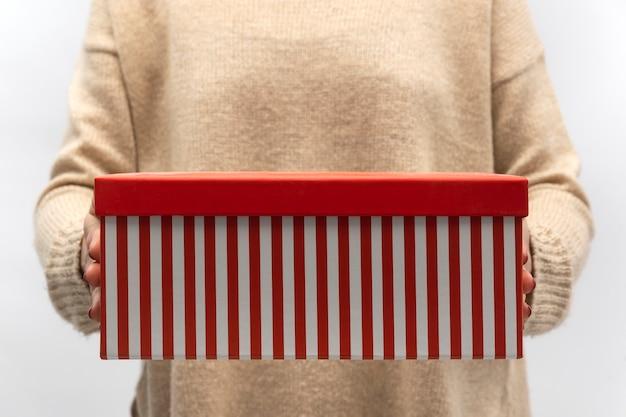 Rot gestreifte weihnachtsgeschenkbox in den weiblichen händen