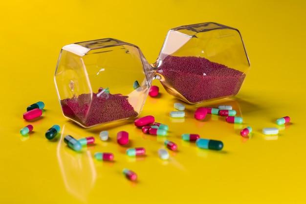 Rot-grüne kapseln, daneben eine sanduhr mit roten sandkörnern. das konzept der pharmakologie.