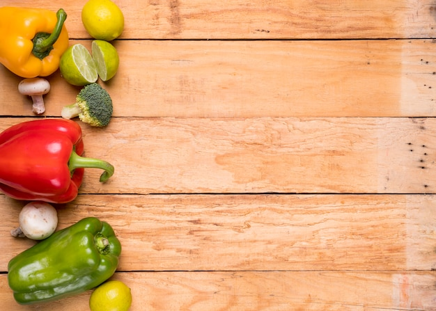 Rot; grüne und gelbe paprikaschoten; pilz; zitrone und brokkoli auf hölzernem schreibtisch