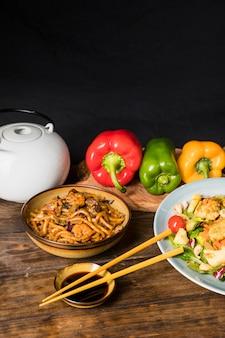 Rot; grüne und gelbe paprikaschoten; teekanne; udon-nudeln und salat mit sojasaucenschüssel mit essstäbchen auf dem schreibtisch