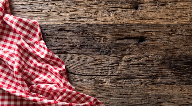 Rot karierte küchentischdecke auf rustikalem holztisch.