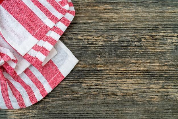 Rot kariertes handtuch auf dem küchentisch. holztisch hintergrund.
