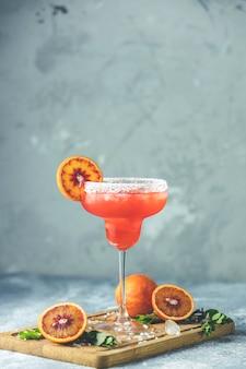 Rot-orangen-margarita-cocktail mit tequila, triple sec, orangensaft, crushed ice und etwas salz am rand eines glases