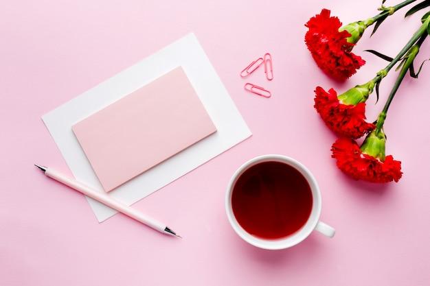 Rot-rosa gegenstände tasse tee, nelke blüht notizblock für text auf rosa pastellhintergrund.
