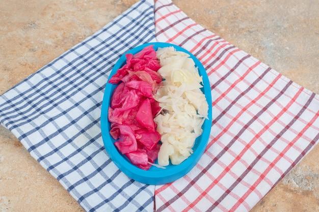 Rot und weiß fermentierter kohl auf blauem teller