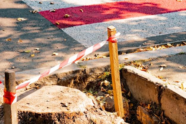 Rot-weiß gestreiftes absperrband an einer kleinen holzstange. baustelle auf dem bürgersteig. zebrastreifen für fußgänger. reparatur. funktioniert