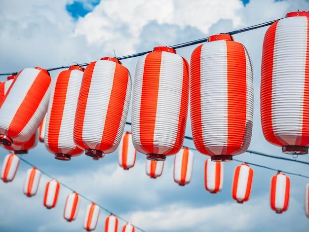 Rot-weißes japanisches papierlaternen chochin, das am bewölkten blauen himmel hängt