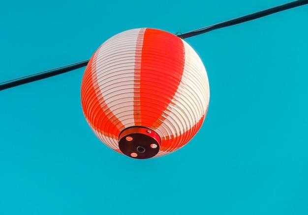 Rot-weißes japanisches papierlaternen chochin, das am blauen himmel hängt