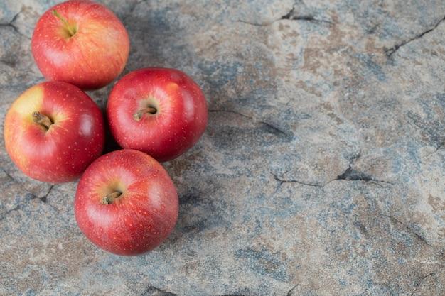 Rote äpfel auf beton isoliert.