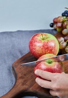 Rote äpfel auf dem holzbrett schneiden.