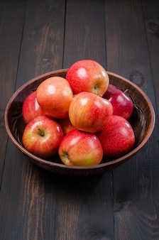 Rote äpfel auf einem dunklen rustikalen hintergrund in einer lehmschüssel. flach liegen.