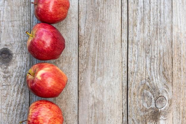 Rote äpfel auf einem hölzernen hintergrund. speicherplatz kopieren.