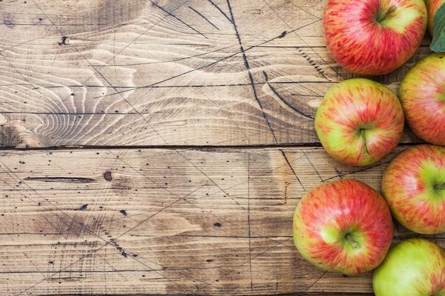 Rote äpfel auf einem hölzernen hintergrund