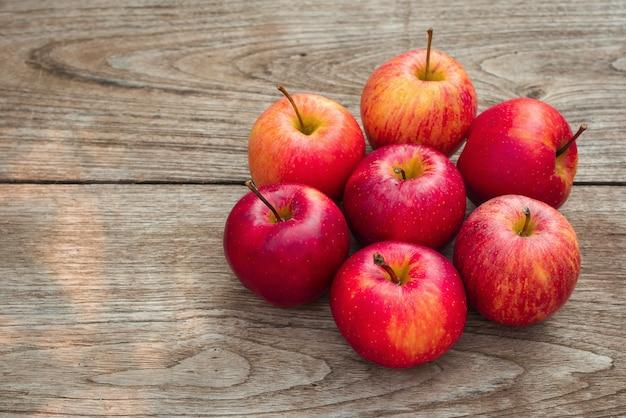 Rote äpfel auf einem holztischhintergrund
