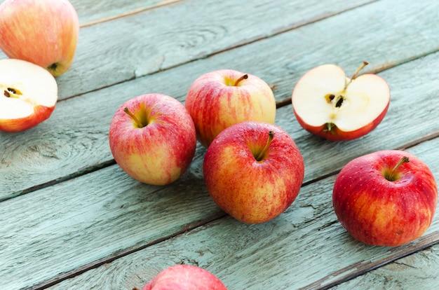 Rote äpfel auf hölzernem hintergrund des türkises. herbsttage.
