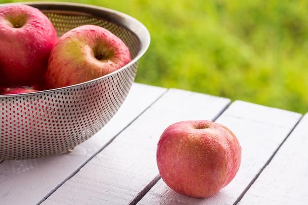 Rote äpfel auf holztisch mit natürlichem grünem hintergrund