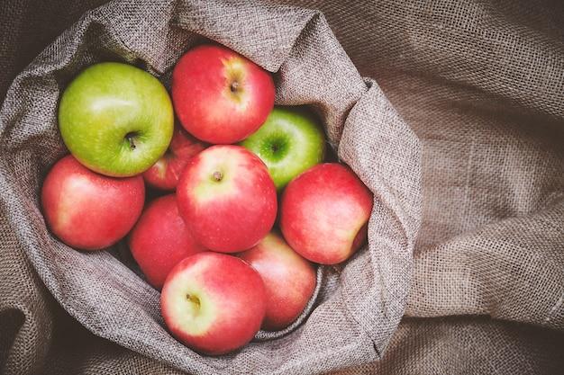 Rote äpfel der draufsicht, grüne äpfel in der korbabdeckung mit brauner leinwandhintergrundbeschaffenheit