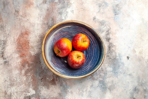 Rote äpfel der draufsicht in der schüssel auf freiem raum der nackten oberfläche