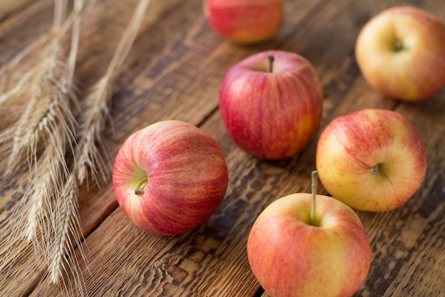 Rote äpfel der nahaufnahme und weizenähren auf hölzernem hintergrund. geringe schärfentiefe. konzentrieren sie sich auf apfel. Premium Fotos