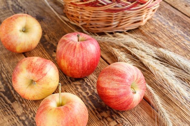 Rote äpfel der nahaufnahme und weizenähren auf hölzernem hintergrund. geringe schärfentiefe. Premium Fotos