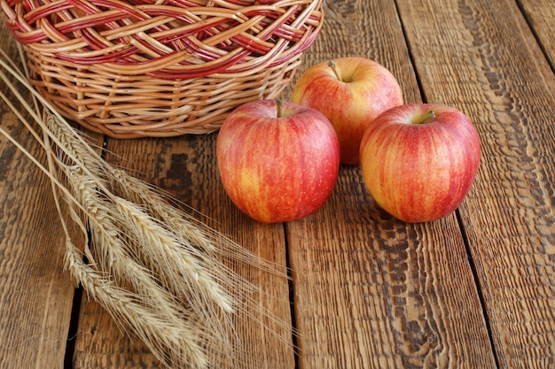 Rote äpfel der nahaufnahme, weidenkorb und weizenähren auf hölzernem hintergrund. geringe schärfentiefe. Premium Fotos