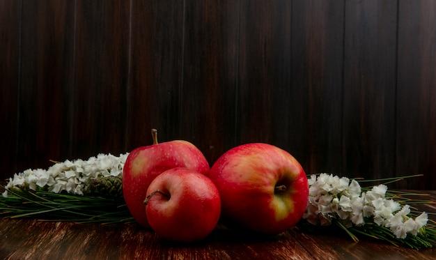Rote äpfel der vorderansicht mit weißen blumen auf einem hölzernen hintergrund
