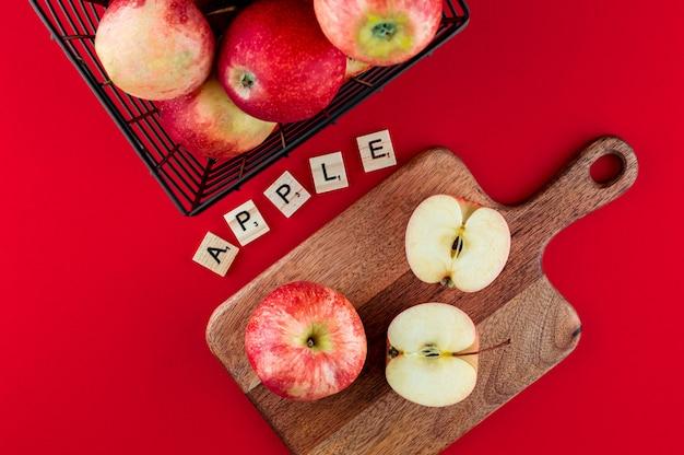 Rote äpfel im metallischen schwarzen korb auf dem tiefroten. draufsicht flach legen zusammensetzung.