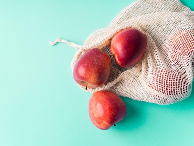 Rote äpfel in wiederverwendbaren baumwollbeuteln