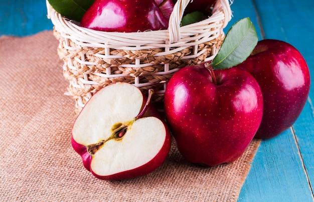 Rote äpfel mit blättern auf dem tisch