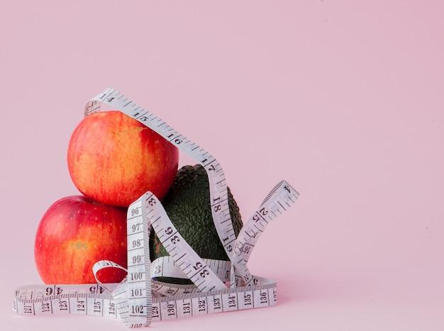 Rote äpfel mit einem maßstab mit avocado auf rosa