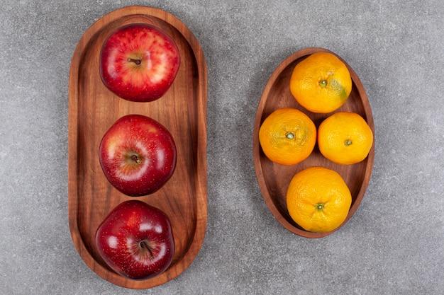 Rote äpfel mit süßen mandarinen auf einem holzbrett