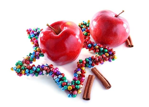 Rote äpfel mit zimtstangen und dekorativem stern isoliert