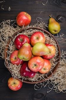 Rote äpfel und birnen auf einem hölzernen dunklen rustikalen hintergrund.