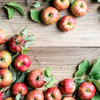 Rote äpfel und blätter draufsicht auf holztisch