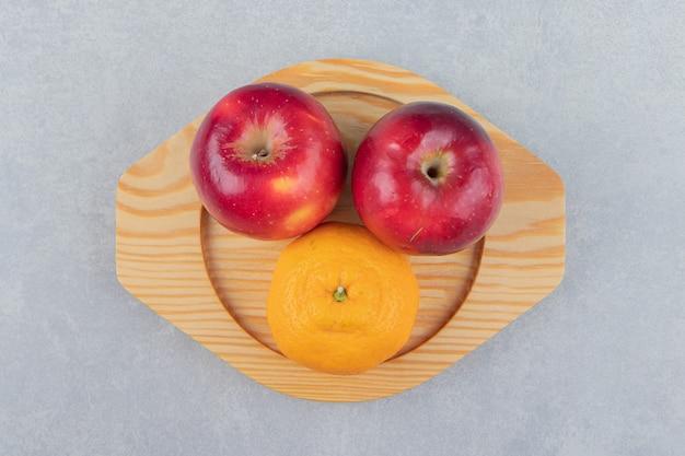 Rote äpfel und mandarine auf holzplatte