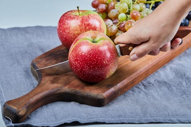 Rote äpfel und weintrauben auf einem holzbrett.