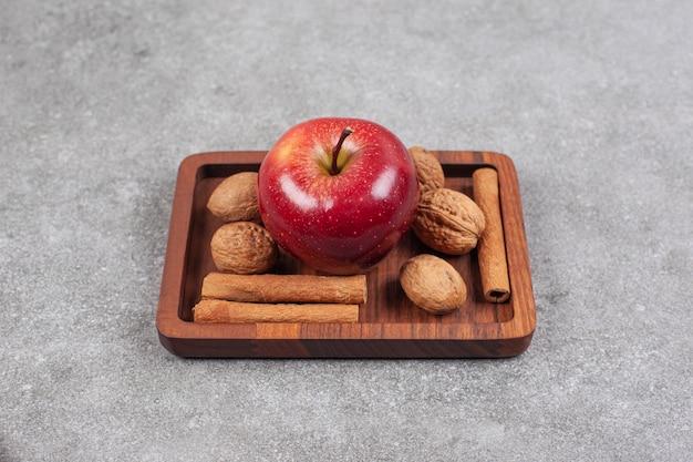 Rote äpfel, walnüsse und zimtstangen auf holzteller