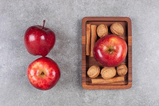 Rote äpfel, walnüsse und zimtstangen auf marmoroberfläche