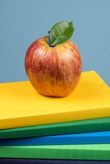 Rote apfelfrucht auf einem bücherstapel, auf der rückseite von schulklassen
