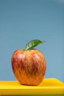 Rote apfelfrucht auf einem bücherstapel, auf der rückseite von schulklassen Premium Fotos