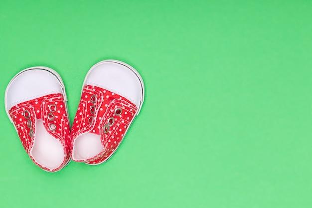 Rote babyschuhe mit weißen tupfen auf grünem hintergrund