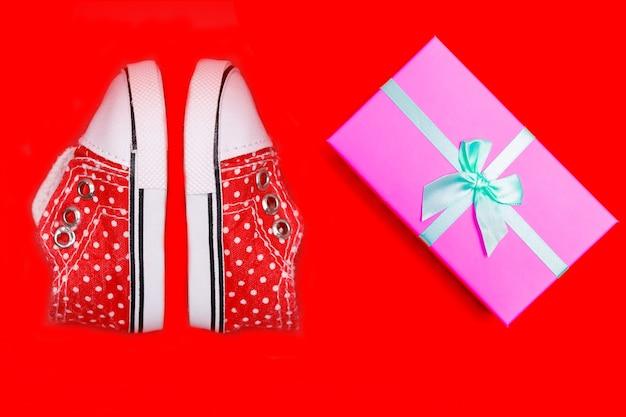 Rote babyschuhe mit weißen tupfen auf rotem grund mit geschenken