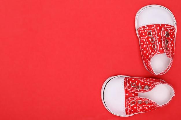 Rote babyschuhe mit weißen tupfen auf rotem grund