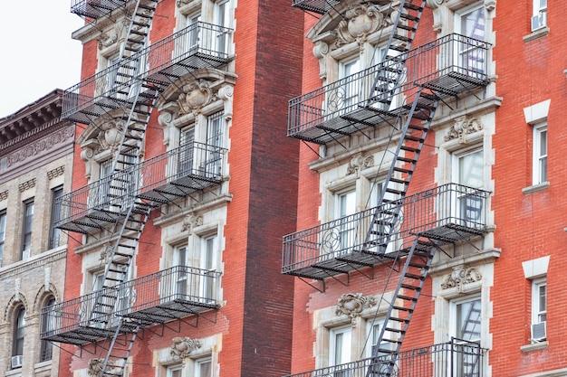 Rote backsteinfassade und feuertreppe. harlem, nyc.